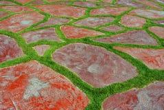 Backgound de roche rouge et d'herbe verte Photographie stock libre de droits