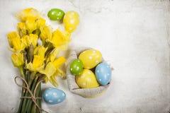 Backgound di Pasqua fuori dalle uova dipinte e dai fiori gialli Immagini Stock