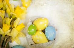 Backgound di Pasqua fuori dalle uova dipinte e dai fiori gialli Fotografie Stock