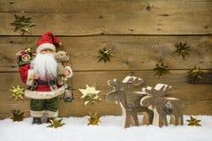 Διακόσμηση Χριστουγέννων: Άγιος Βασίλης με τον ξύλινο τάρανδο στο backgr Στοκ Εικόνες