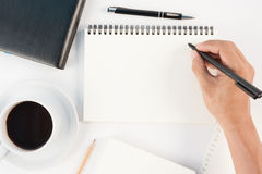 杯在白色backgr的热的咖啡和人手文字笔记本 免版税库存图片