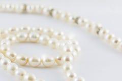 在白色backgro隔绝的美丽的乳脂状的珍珠项链曲线 免版税库存图片