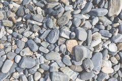 海石头或湿光滑的黑石头在海滩作为backgro 库存图片