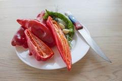 Backgro verde e rosso del peperone dolce Includa le verdure ed il pepe organici freschi sul pavimento di legno Immagini Stock