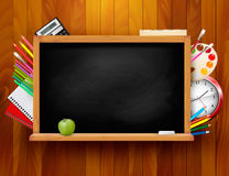 有学校用品的黑板在木backgrou 免版税库存图片