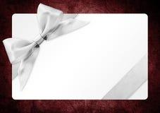 Κάρτα δώρων με το ασημένιο τόξο κορδελλών που απομονώνεται στο κόκκινο backgrou Στοκ Εικόνα