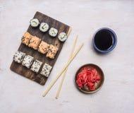 自创寿司卷品种用黄瓜、三文鱼和螃蟹用酱油和姜,亚洲烹调木土气backgrou 免版税库存图片