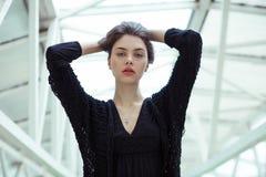 忧郁年轻美丽的深色的妇女画象接触她的在一轻的几何模糊的backgrou的一件黑boho礼服的头发 免版税图库摄影