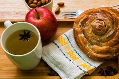 Backgroud di legno della mela e del tè della prima colazione del rotolo di cannella fotografia stock libera da diritti