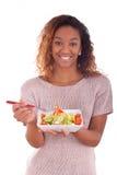 吃沙拉的非裔美国人的妇女,隔绝在白色backgroun 库存照片