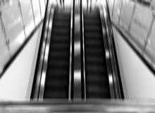 Backgroun blanco y negro vertical de la escalera móvil del aeropuerto de la falta de definición de movimiento Imágenes de archivo libres de regalías