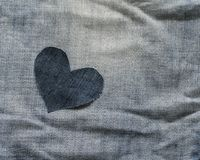 Background of alone denim heart lies in rumpled blue fabric Royalty Free Stock Photos