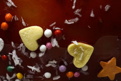 Background Apple in a caramel glaze. Strew of hearts stars balls. Close-up. Stock Photography