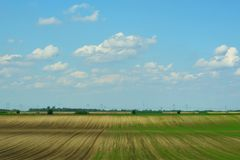 Background from an arable land and the sky with clouds. In spring Royalty Free Stock Image