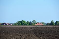 Background from an arable land and the sky. With houses nearby Royalty Free Stock Images