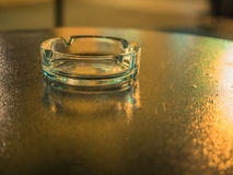 Background of the ashtray on the black table close up. Picture of the glassy ashtray close up. Ashtray laying on the blurred surface of the table. Blurred Stock Photos