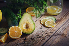 Background with assorted green vegetables. Apple, avocado, cucumber, lemon and detox water on rustic wooden table top. Healthy food, detox, dieting, vegetarian Stock Image