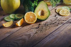 Background with assorted green vegetables. Apple, avocado, cucumber, limon and detox water on rustic wooden table top. Healthy food, detox, dieting, vegetarian Royalty Free Stock Image