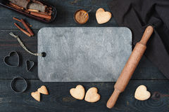 Background with baked cookies-hearts and kitchen utensils. Baked cookies-hearts and kitchen utensils on the vintage wooden table, background with empty space Stock Image