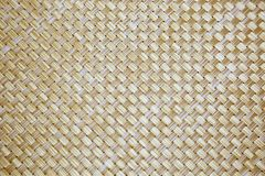 Background plastic with a diagonal weaving of beige color. A background of bamboo with a diagonal weave, a napkin of beige and brown color Royalty Free Stock Photo
