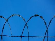 Background of a barbwire fence against a blue sky forming a geometric pattern of archs horizontal stock image