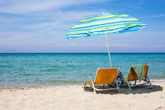Background with Beach chairs and colorful umbrella on sandy beach Stock Photo