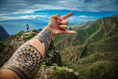 Background of the beautiful mountain landscape. Man`s hand showing rock onsign against background of the beautiful mountain landscape stock photo