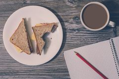 Background of bitten cheese sandwich on a white round plate, cup of hot coffee, open notebook with a pencil on it. Top view. Unhea. Lthy fast eating snack at Stock Images