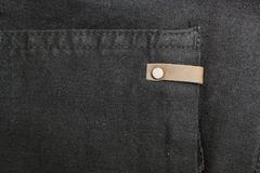 Background of black denim with copper elements and seams. Space for text stock photography