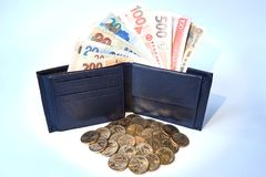 Background, black men`s wallet with bills of various currencies and yellow metal dollars, isolated stock photos