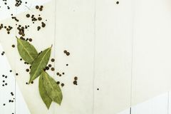 Background of black pepper and bay leaves, white wooden table. Space for text or dishes royalty free stock images