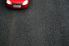 Background of black tarmac of street. With motion blurred front of red car Stock Photography