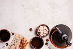 Background with black teapot and bowls with tea. Background with black teapot and bowls with spicy tea on the gray textured table, copy space Royalty Free Stock Photo