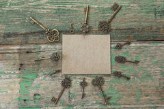 Background with blank card and antique keys on old painted woode Stock Image