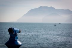Background of a blue panoramic touristic telescope overlooking the sea with a boat stock photography