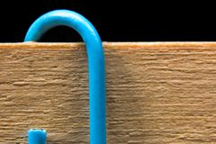 Background with blue paper clip and wooden surface macro Stock Photos