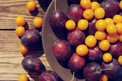 Background with blue plums and a yellow cherry plums Stock Images