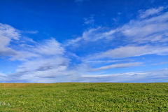 Background of blue sky, cloud and meadow. On cloudy day Stock Photos
