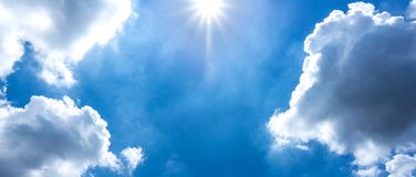 Sun is shinning in the sky and cloud. Background of blue sky and cumulus cloud with sun is shining at noon time royalty free stock photo