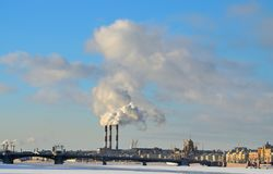 Smoke from factory chimneys. On the background of blue sky smoke rises from factory chimneys stock photo
