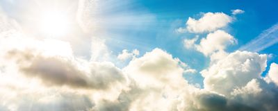 Blue sky with white clouds and sun. A background of the blue sky with white cumulus clouds and bright sun Royalty Free Stock Photography