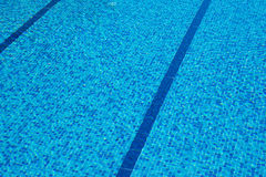 Background of a blue tiled pool with clear cool rippling water Royalty Free Stock Images