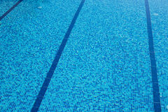 Background of a blue tiled pool with clear cool rippling water Stock Images