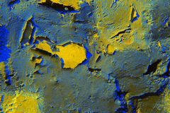 The background of blue and yellow paint with cracks on a rough wall. stock photography