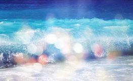 Background of blurred beach and sea waves with bokeh lights. Sandy beach with turquoise water, bright white sun lights bokeh, travel and summer holidays stock photography