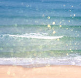 Background of blurred beach and sea waves with bokeh lights, vintage filter. Royalty Free Stock Photography