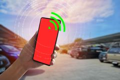 Background blurred parking,View holding smartphone turn on communication with vehicle for position and safety. Empty space for. Background blurred parking ,.View stock images
