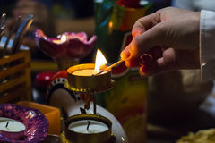 Background blurred woman's hand lights a candle in a candlestick with a match Stock Image