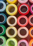 Background from bobbins with multicolored thread Stock Images