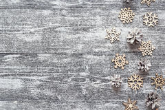 Background with a border of decorative wooden snowflakes and whi Stock Photos